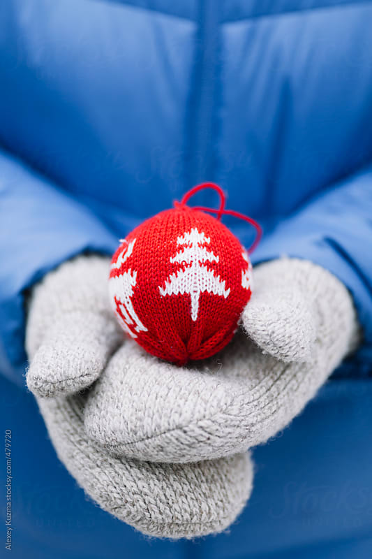 Hands in large mitten  with red Christmas Ornament. by Alexey Kuzma for Stocksy United