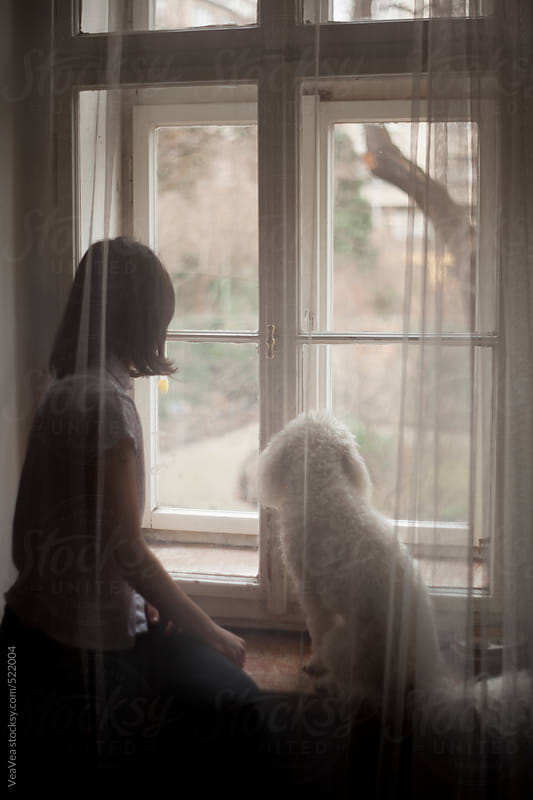 Young woman and a white poodle looking through the window from the back  by VeaVea for Stocksy United