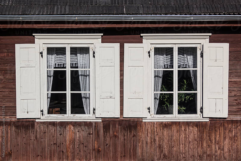 Two windows in a traditional wooden house in rural Lithuania by Melanie Kintz for Stocksy United