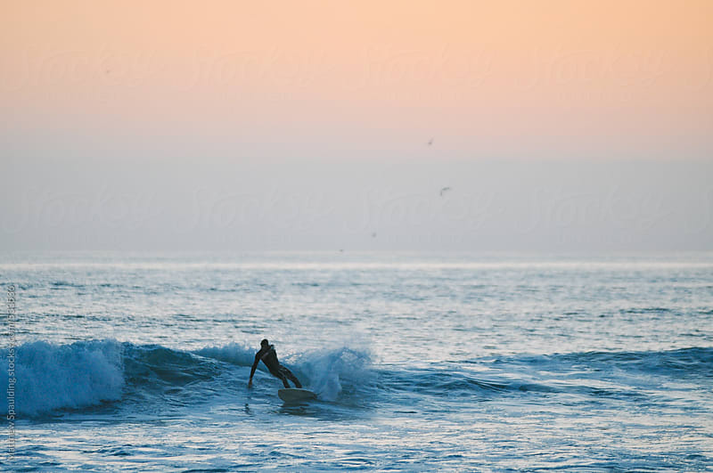 Person surfing alone on ocean waves at sunset by Matthew Spaulding for Stocksy United
