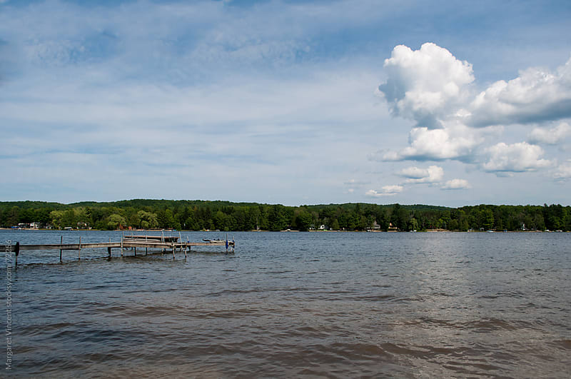 lake with dock and clouds by Margaret Vincent for Stocksy United