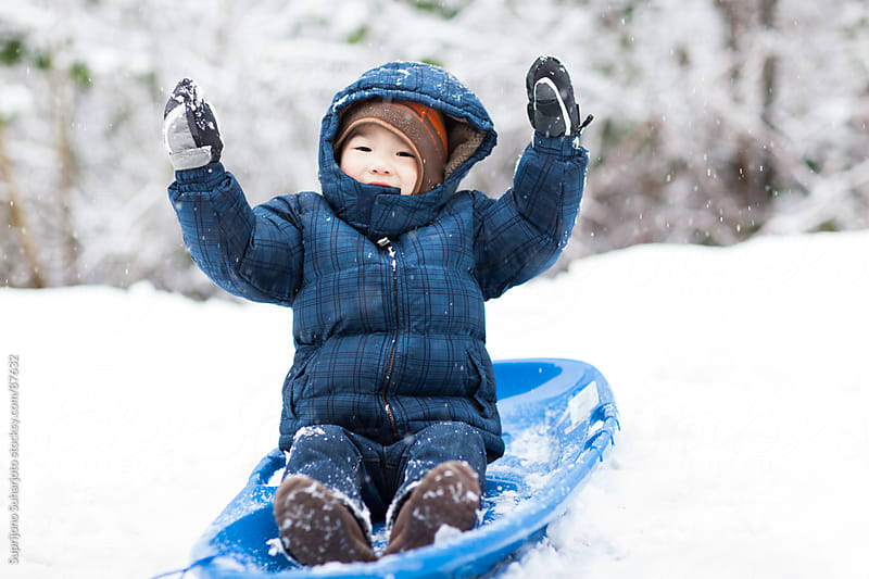 Asian boy sledding in the snow by Suprijono Suharjoto for Stocksy United