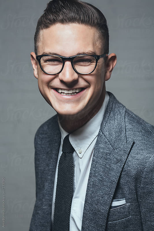 A handsome young man wearing black rimmed eye glasses smiling by Ania Boniecka for Stocksy United