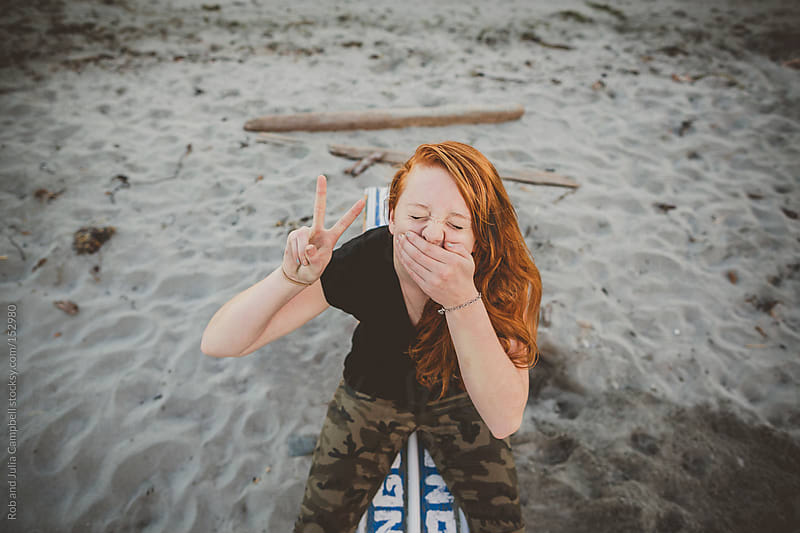 Portrait of redhead teenage girl sitting at the beach being goof by Rob and Julia Campbell for Stocksy United