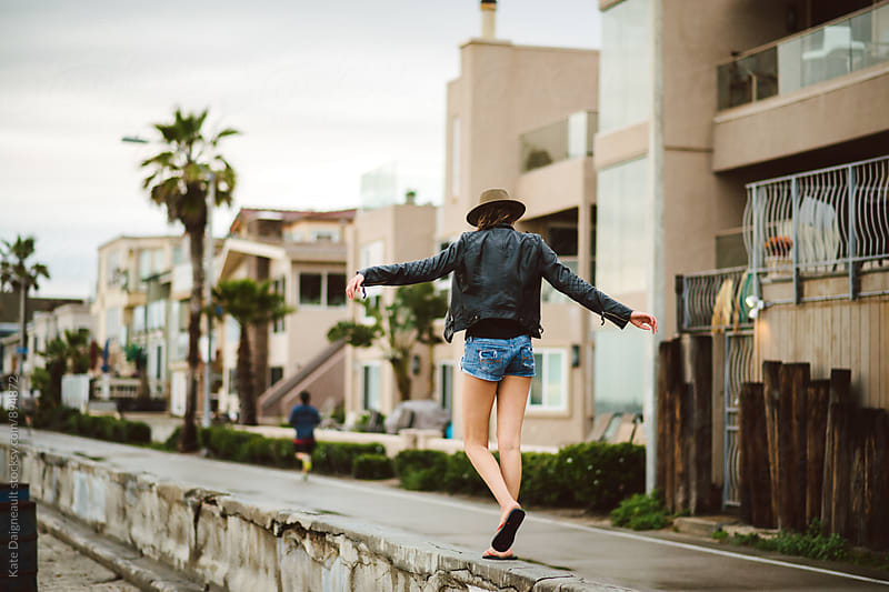 Trendy teenage girl walking on beach wall on a California boardwalk by Kate Daigneault for Stocksy United