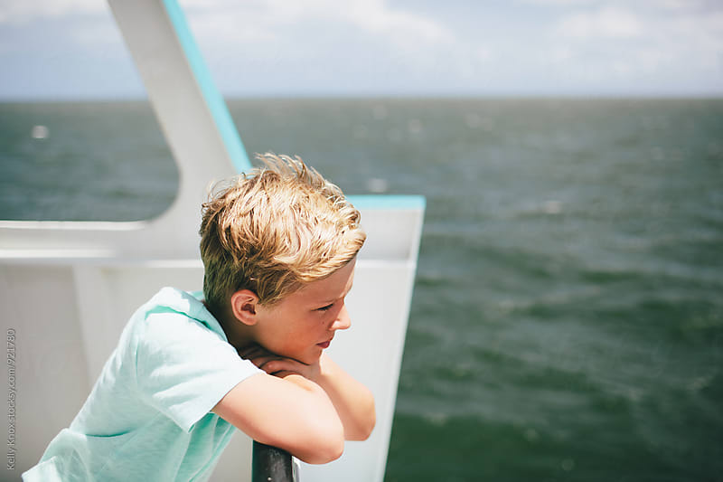 boy looking at the ocean from a boat on a sunny day by Kelly Knox for Stocksy United