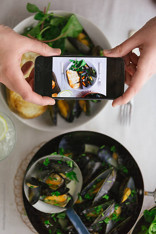 Woman takes a photo of her meal on her smartphone by Kirsty Begg for Stocksy United