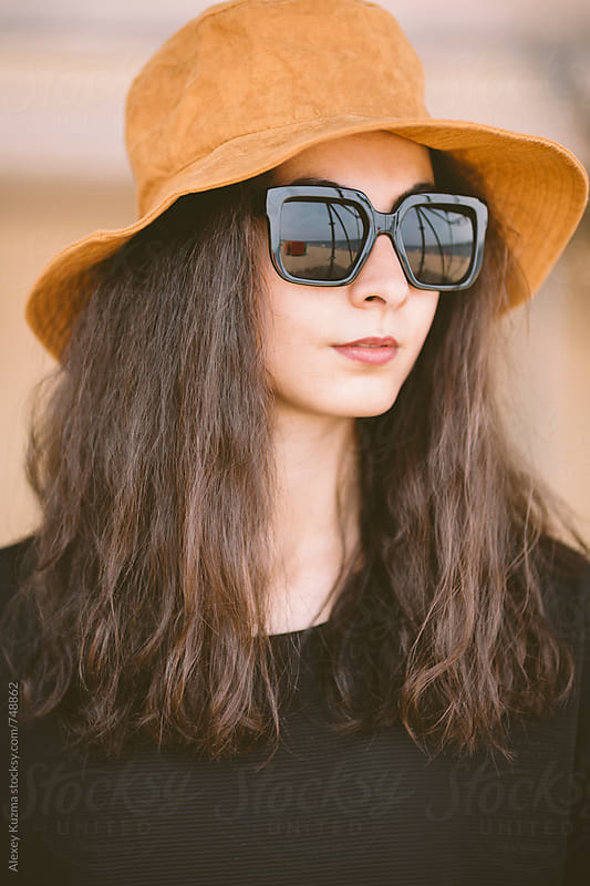 closeup of portrait of real young woman with hat and sunglasses by Alexey Kuzma for Stocksy United