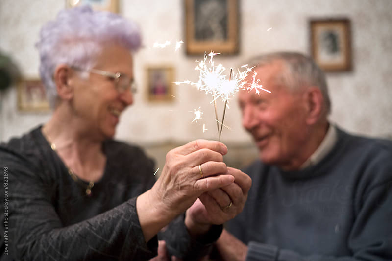 Happy senior couple in their eighties holding sparkler together  by Jovana Milanko for Stocksy United