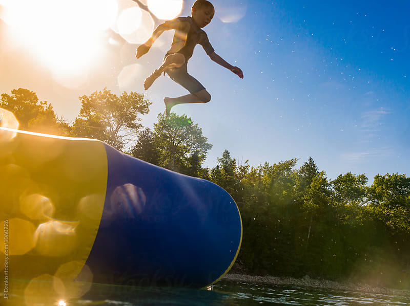 Little Boy Jumping Into Summer Lake From Water Trampoline At Cottage at Sunset by JP Danko for Stocksy United