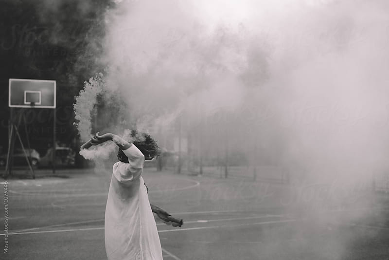 Anonymous Woman Holding Smoke Bomb  by Mosuno for Stocksy United