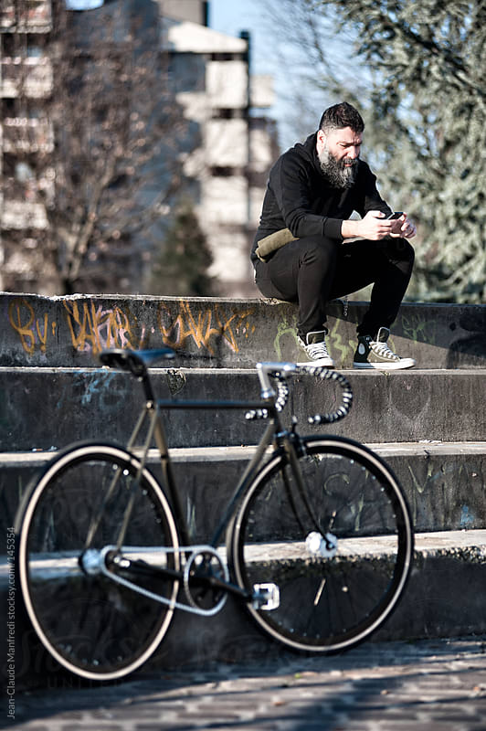 Hip man takes a break with his fixed gear bike in a suburb of Milano checking mobile phone by Jean-Claude Manfredi for Stocksy United