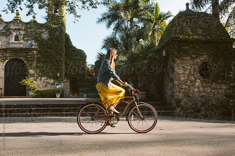 Woman in skirt riding bicycle by Stephen Morris for Stocksy United