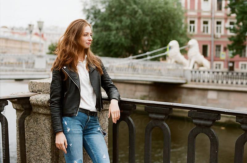 Young woman standing close to a bridge by Liubov Burakova for Stocksy United
