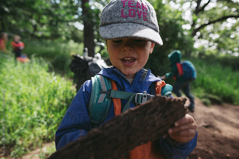 Young caucasian looking at tree bark at nature preschool by Rob and Julia Campbell for Stocksy United
