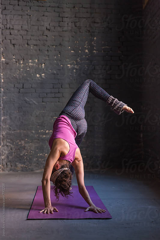 Vertical shot of a young woman practicing yoga  by Jovo Jovanovic for Stocksy United