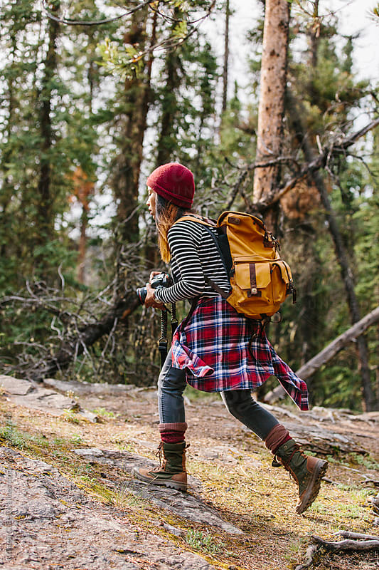 A woman with a camera & a backpack exploring the outdoors  by Kristen Curette Hines for Stocksy United