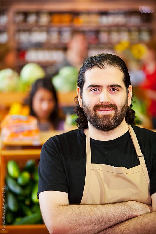Market: Male Grocer with Shoppers Behind by Sean Locke for Stocksy United