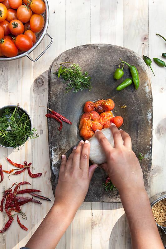 Hands making tomato aachar. by Shikhar Bhattarai for Stocksy United