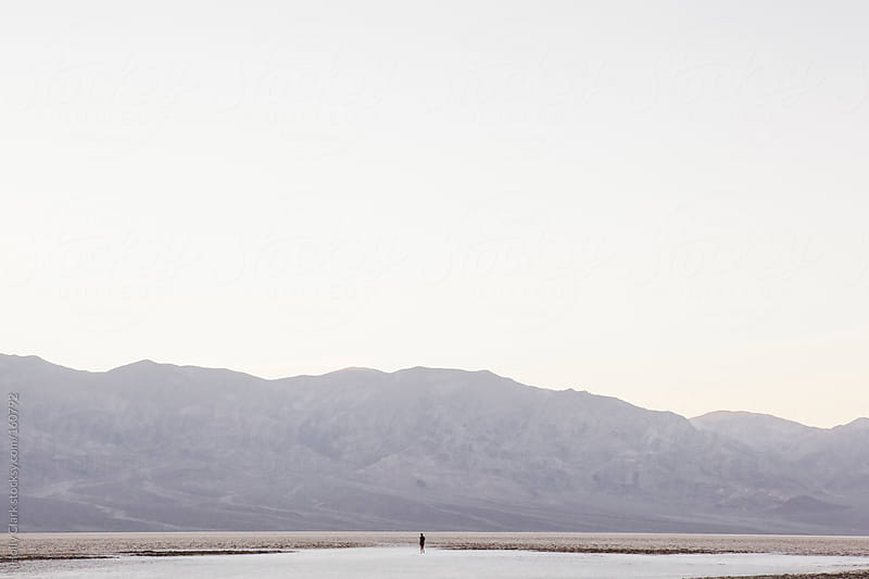 A photographer walks on the salt flats in Death Valley in the la by Holly Clark for Stocksy United