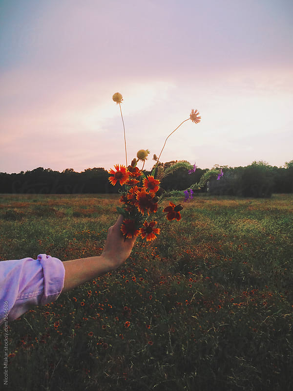 Girl holding wildflowers at sunset by Nicole Mlakar for Stocksy United