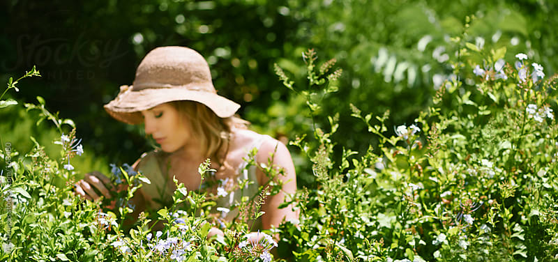 Beautiful girl gardening in Summer by Aila Images for Stocksy United
