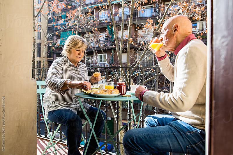 Elderly couple having a breakfast on balcony. by BONNINSTUDIO for Stocksy United