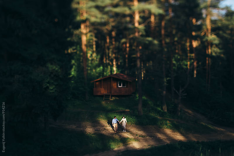 Young couple together in the spotlight in the forest by Evgenij Yulkin for Stocksy United