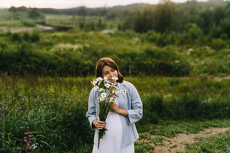 Pregnant female holding the camomile bouquet by Evgenij Yulkin for Stocksy United