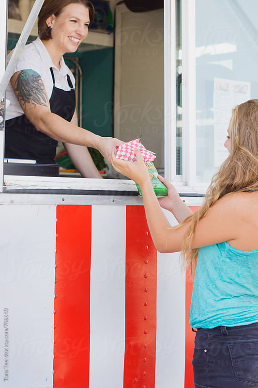 Smiling food vendor passes food to customer through window by Tana Teel for Stocksy United