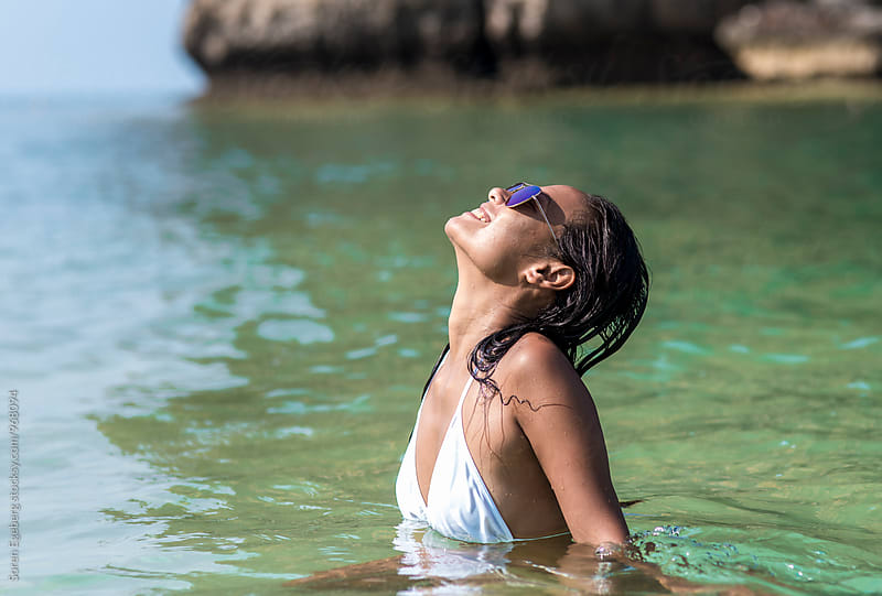Beautiful young woman swimming in the sea wearing sunglasses by Soren Egeberg for Stocksy United