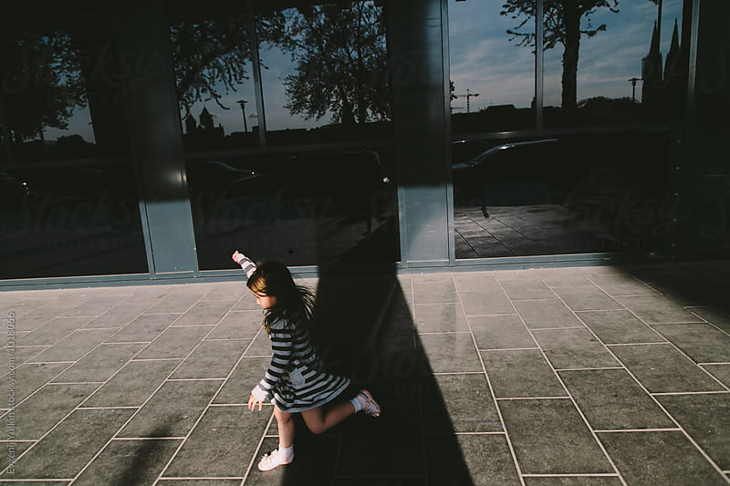 Little girl running  through the sunbeam along the street  by Evgenij Yulkin for Stocksy United