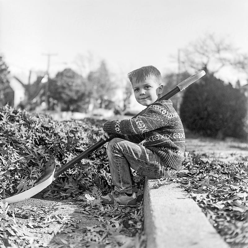 Young boy looking exhausted after helping to do leaf clean up  by Cameron Whitman for Stocksy United