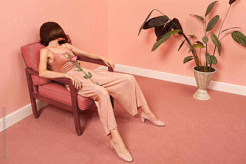 woman sitting on an armchair in a pink room by Ulaş and Merve for Stocksy United