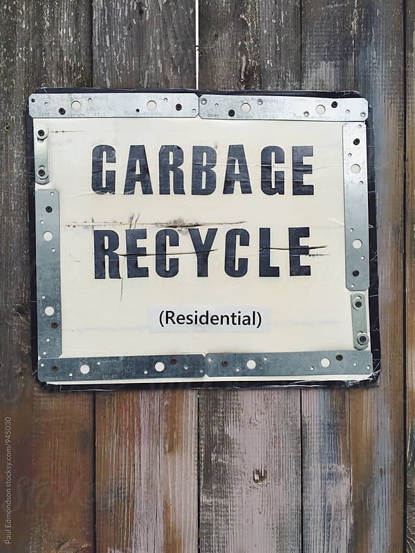 Garbage and recycling sign posted on fence by Paul Edmondson for Stocksy United
