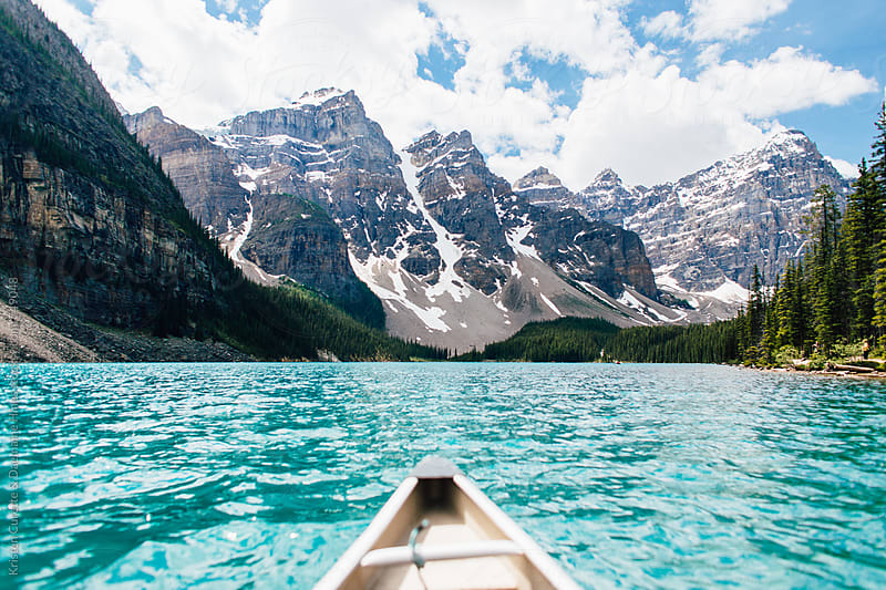 First person view canoeing through clear blue water by Kristen Curette Hines for Stocksy United