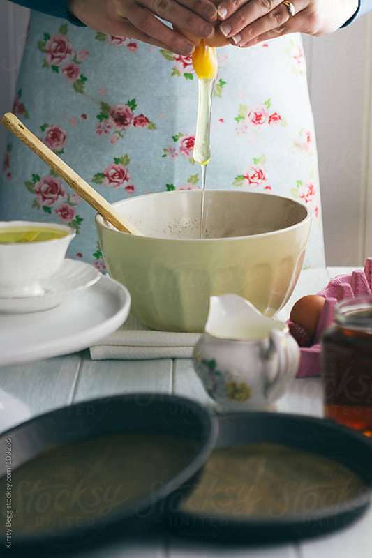Woman adding egg into mixing bowl to make chocolate cake by Kirsty Begg for Stocksy United