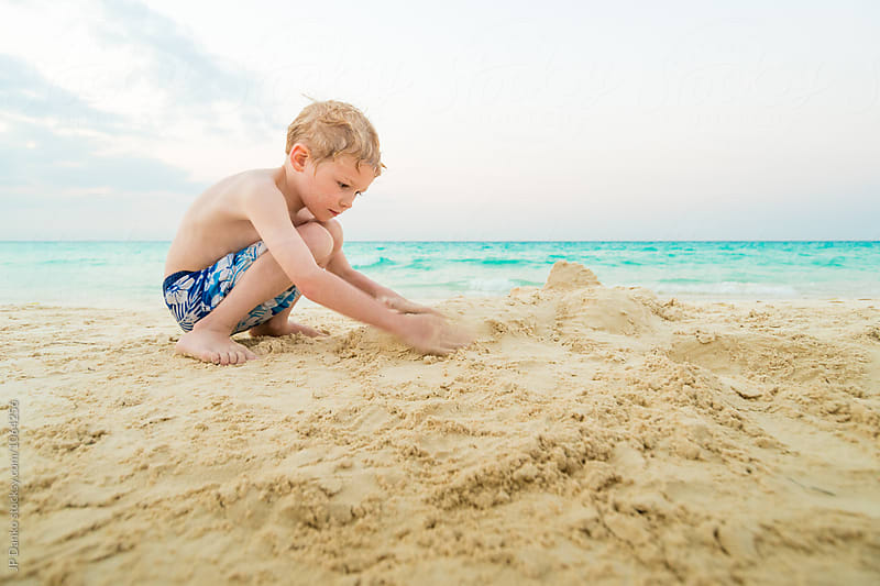 Boy Building Sand Castle on White Sand Tropical Beach WIth Turqu