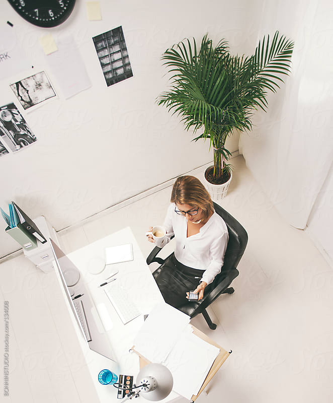 Aerial view of mature business woman working at office. by BONNINSTUDIO for Stocksy United