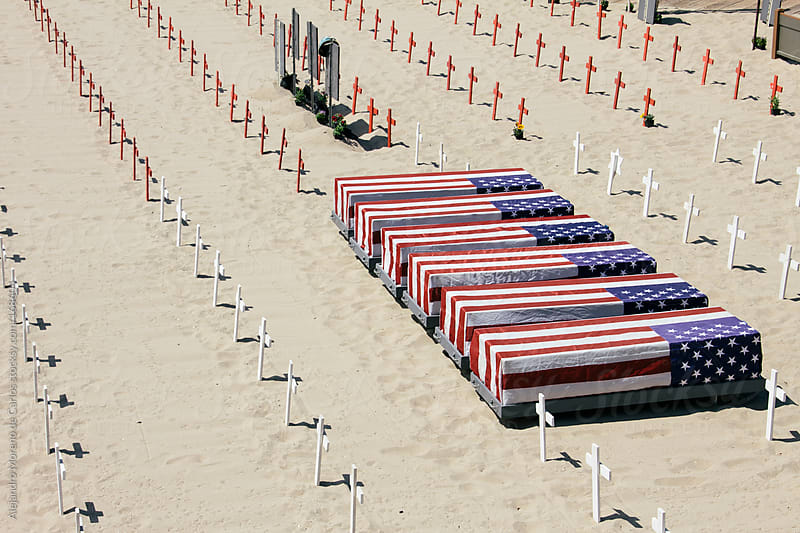 Coffins covered with american flag on a memorial on the beach by Alejandro Moreno de Carlos for Stocksy United