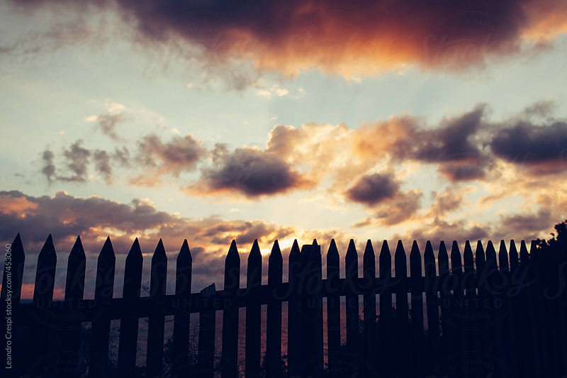 A wooden fence with a beautiful cloudy sky at background by Leandro Crespi for Stocksy United