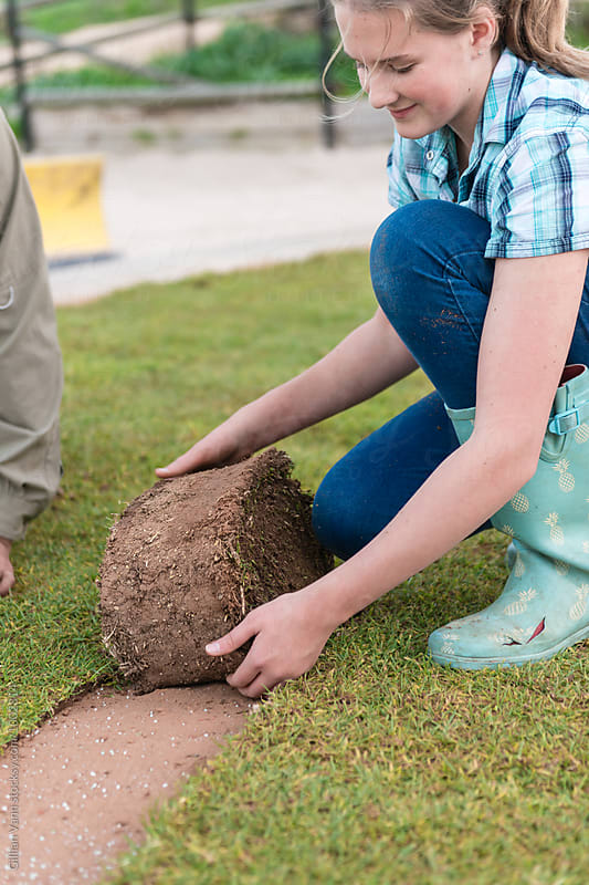 a garden makeover project, teen girl helping to lay turf by Gillian Vann for Stocksy United