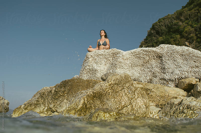 Woman Meditating on the Rocks  by Brkati Krokodil for Stocksy United