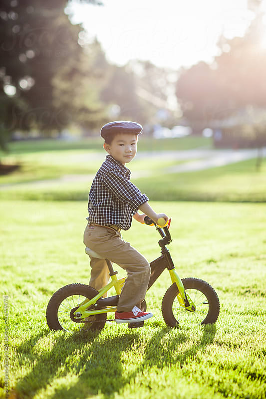 Asian kid riding a bicycle outdoor by Suprijono Suharjoto for Stocksy United