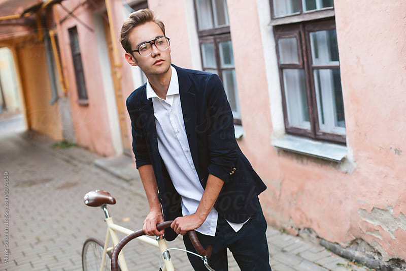 Young handsome fashion man walking on the street with bicycle  by Viktor Solomin for Stocksy United