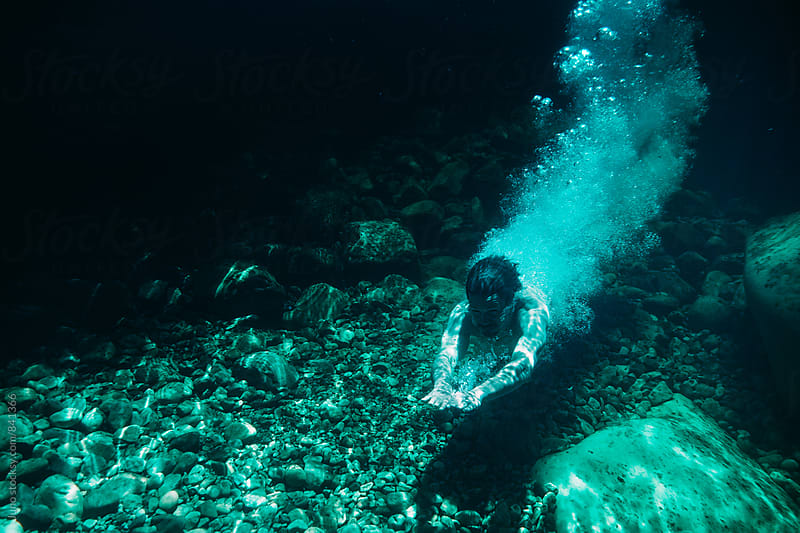 Man diving into a rock pool of a mountain stream by Micky Wiswedel for Stocksy United