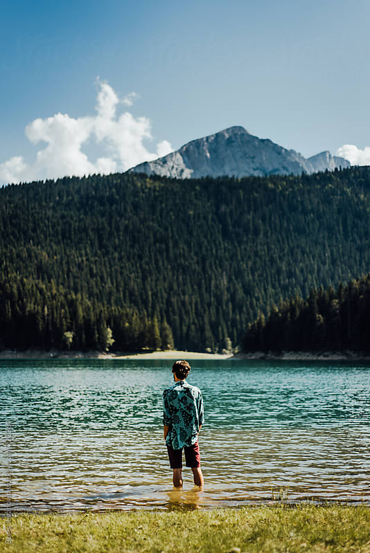 Man in shirt entering the lake by Boris Jovanovic for Stocksy United