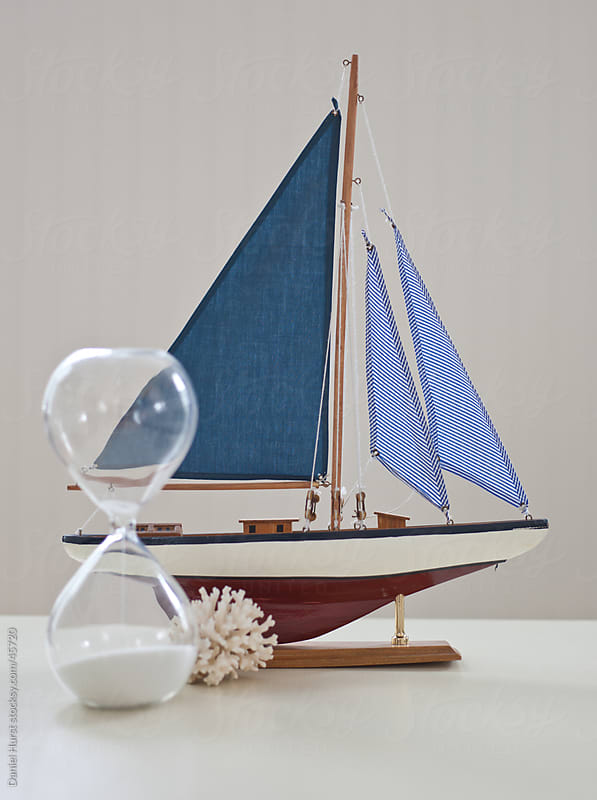 Coastal still life with sailboat and hourglass by Daniel Hurst for Stocksy United