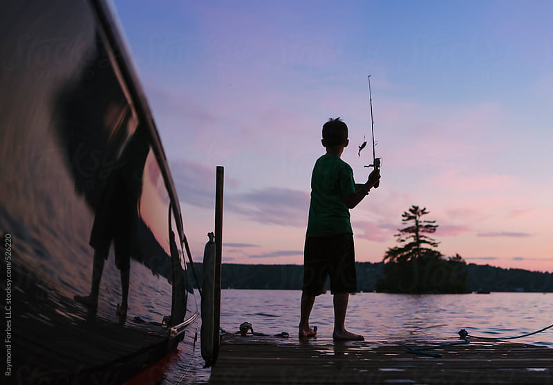 Boy Fishing on Lake in New Hampshire by Raymond Forbes LLC for Stocksy United