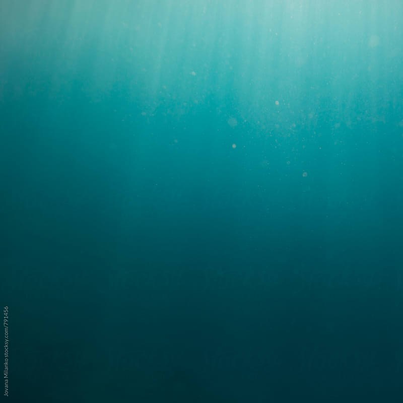 Dark blue under water empty sea  background with sunrays going trough the surface by Jovana Milanko for Stocksy United